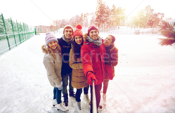 happy friends with smartphone on ice skating rink Stock photo © dolgachov
