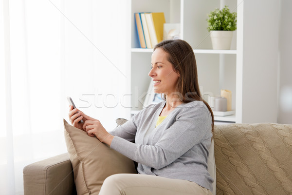 счастливым женщину обмен сообщениями смартфон домой технологий Сток-фото © dolgachov