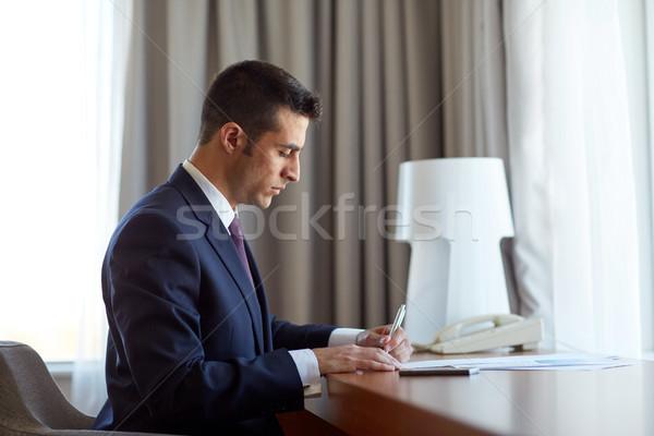 Zakenman papieren werken hotelkamer zakenlieden papierwerk Stockfoto © dolgachov