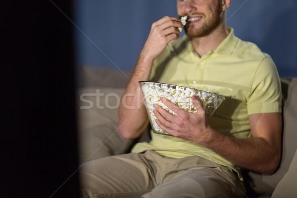 Adam patlamış mısır izlerken tv gece Stok fotoğraf © dolgachov