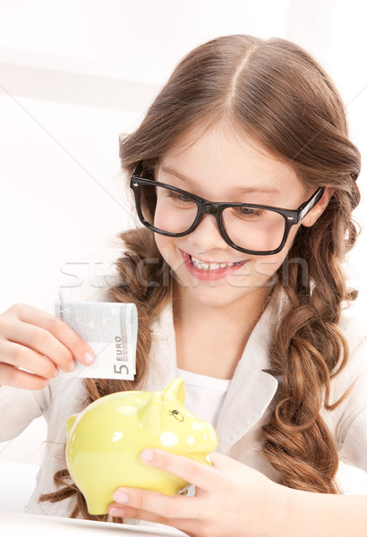 little girl with piggy bank and money Stock photo © dolgachov