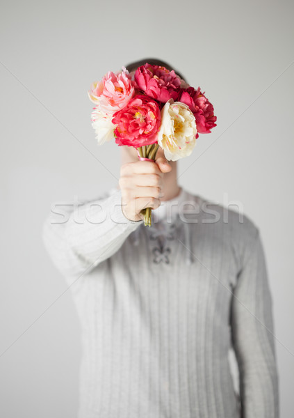 man covering his face with bouquet of flowers Stock photo © dolgachov