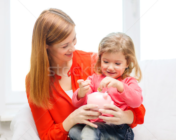 happy mother and daughter with small piggy bank Stock photo © dolgachov