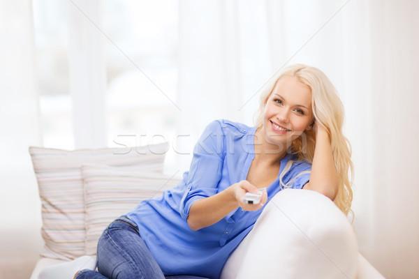 Sorridente jovem controlar casa televisão Foto stock © dolgachov