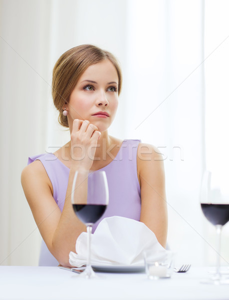 upset woman with glass of whine waiting for date Stock photo © dolgachov