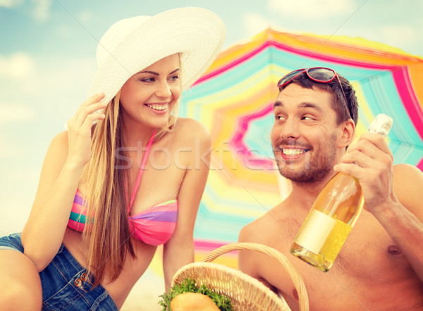 smiling couple having picnic on the beach Stock photo © dolgachov