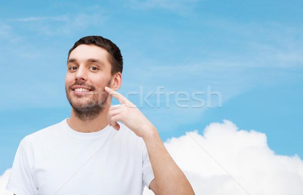 Sorridente jovem homem bonito indicação bochecha saúde Foto stock © dolgachov