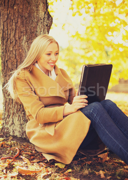 woman with tablet pc in autumn park Stock photo © dolgachov