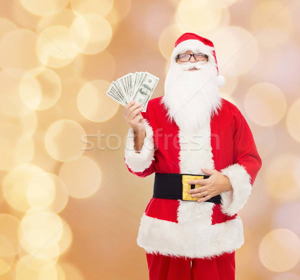 man in costume of santa claus with dollar money Stock photo © dolgachov