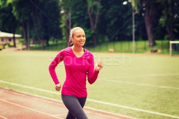 smiling woman running on track outdoors Stock photo © dolgachov