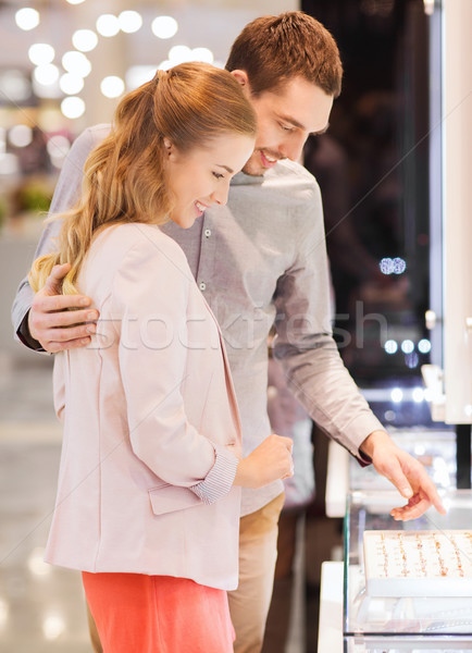 happy couple choosing engagement ring in mall Stock photo © dolgachov