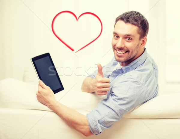 Stock photo: smiling man working with tablet pc at home