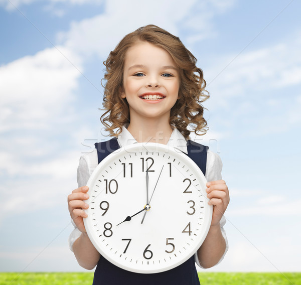 smiling girl holding big clock Stock photo © dolgachov