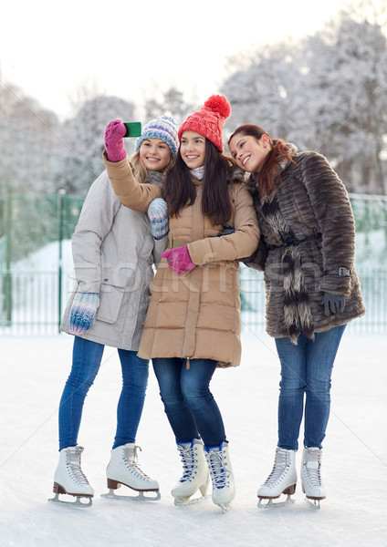 happy young women with smartphone on skating rink Stock photo © dolgachov