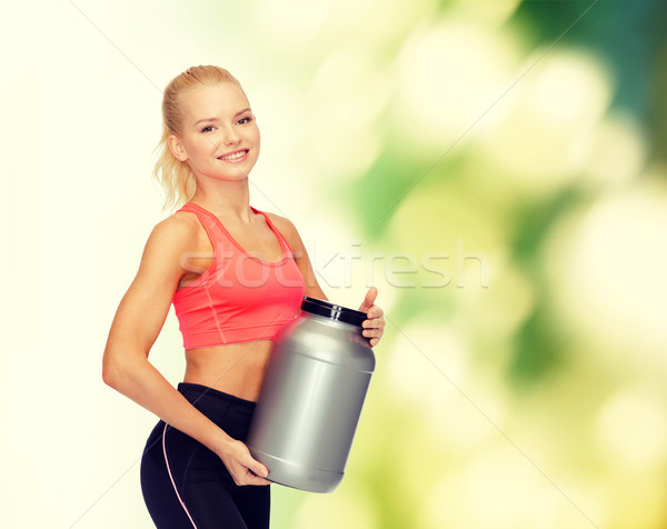 smiling sporty woman with jar of protein Stock photo © dolgachov