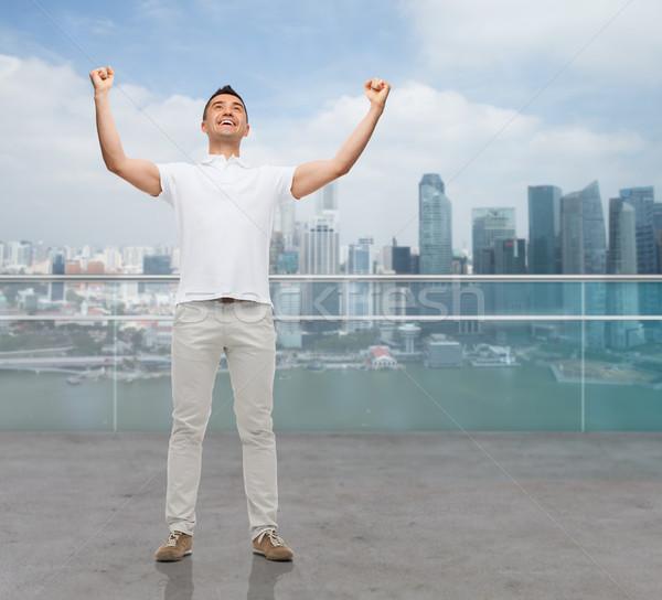 happy man with raised hands Stock photo © dolgachov