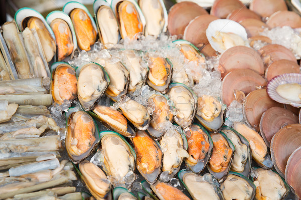 oysters or seafood on ice at asian street market Stock photo © dolgachov