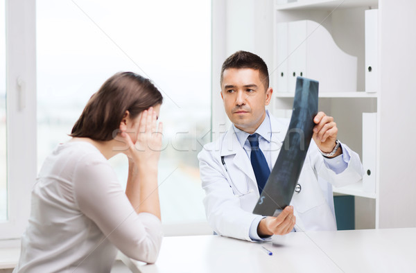 smiling male doctor in white coat looking at x-ray Stock photo © dolgachov