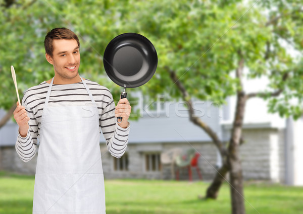 happy man or cook in apron with pan and spoon Stock photo © dolgachov