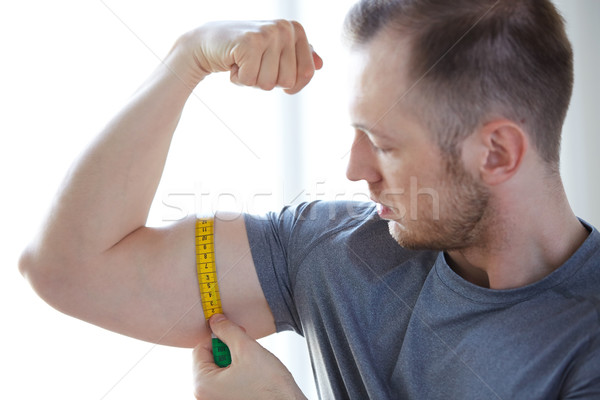 close up of male hands with tape measuring bicep Stock photo © dolgachov