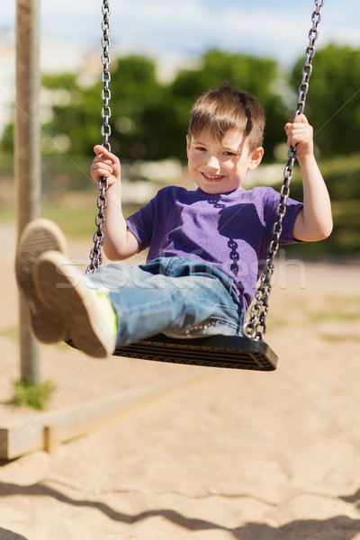happy little boy swinging on swing at playground Stock photo © dolgachov