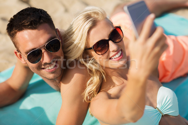 happy couple in swimwear walking on summer beach Stock photo © dolgachov