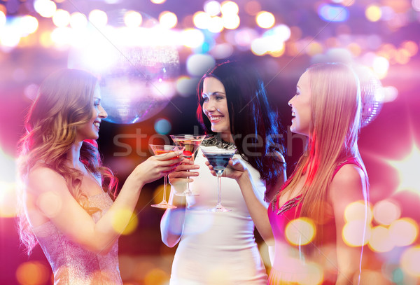 smiling women with cocktails at night club Stock photo © dolgachov