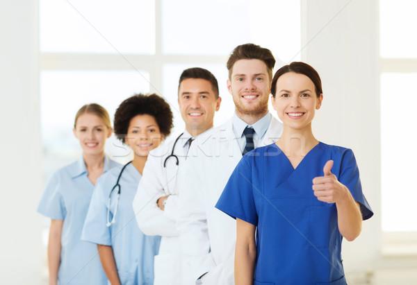 happy doctors showing thumbs up at hospital Stock photo © dolgachov
