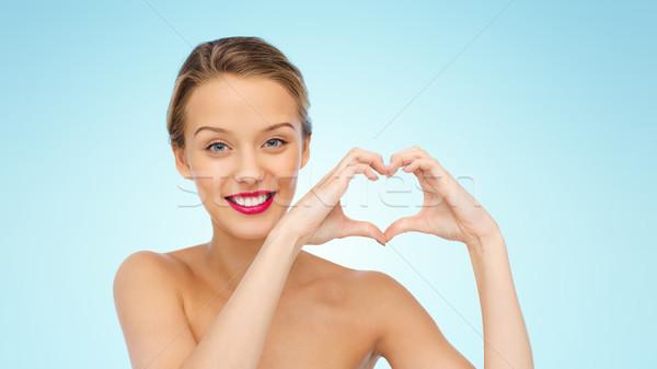 Souriant jeune femme forme de coeur signe de la main beauté Photo stock © dolgachov