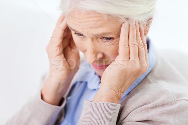 face of senior woman suffering from headache Stock photo © dolgachov