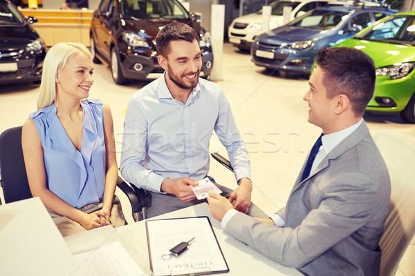happy couple with car dealer in auto show or salon Stock photo © dolgachov