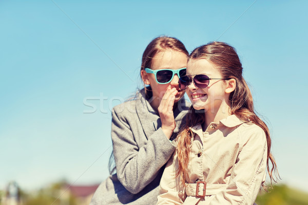 happy girl whispering secret to her friends ear Stock photo © dolgachov