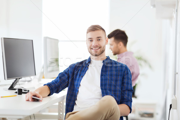 happy creative man with cellphone at office Stock photo © dolgachov