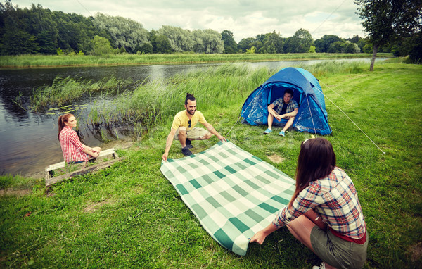 happy friends laying picnic blanket at campsite Stock photo © dolgachov