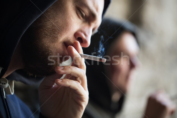 Stock photo: close up of young man smoking cigarette outdoors