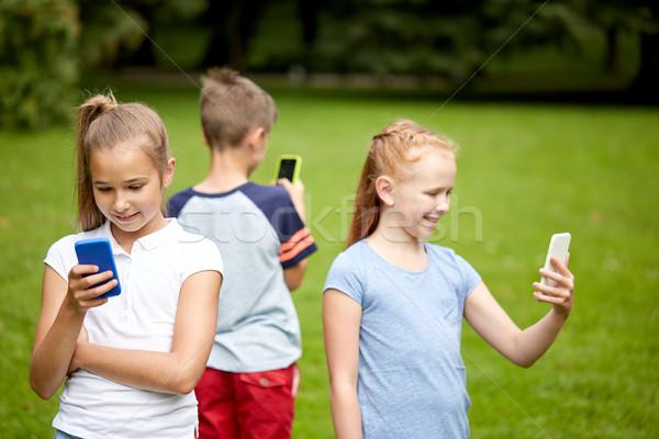 Gyerekek okostelefonok játszik játék nyár park Stock fotó © dolgachov