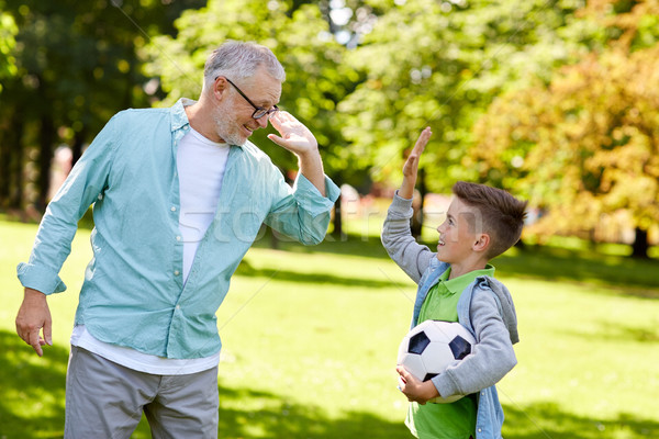 old man and boy with soccer ball making high five Stock photo © dolgachov