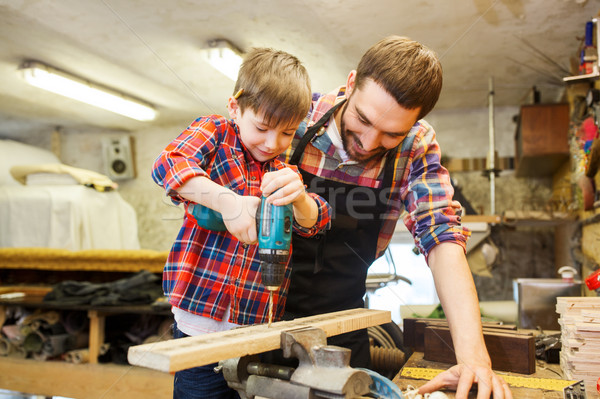 father and son with drill working at workshop Stock photo © dolgachov