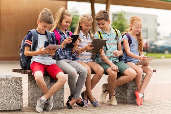 group of happy elementary school students talking Stock photo © dolgachov
