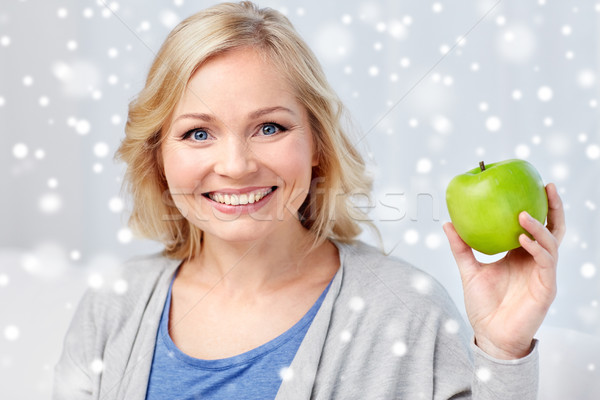 happy middle aged woman with green apple at home Stock photo © dolgachov