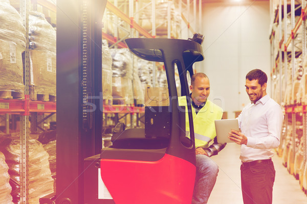 men with tablet pc and forklift at warehouse Stock photo © dolgachov