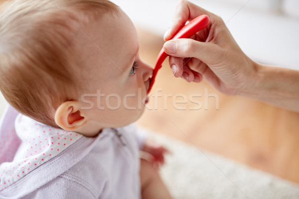 hand with spoon feeding little baby at home Stock photo © dolgachov