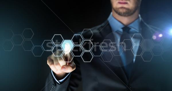 businessman touching virtual hexagonal projection Stock photo © dolgachov