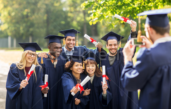 students or bachelors photographing by smartphone Stock photo © dolgachov
