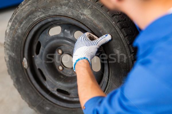 mechanic with wheel tire at car workshop Stock photo © dolgachov