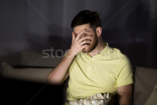 scared man watching tv and eating popcorn at night Stock photo © dolgachov