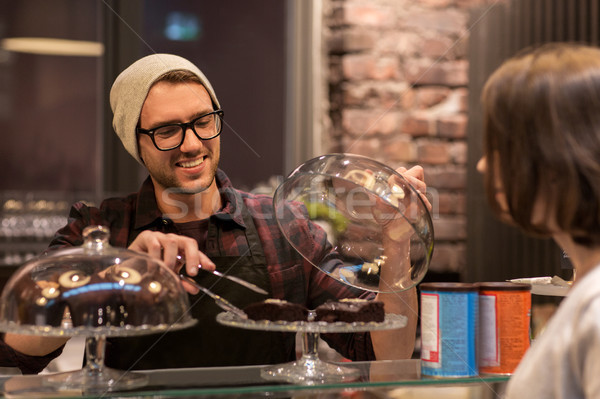 man or barman with cakes serving customer at cafe Stock photo © dolgachov