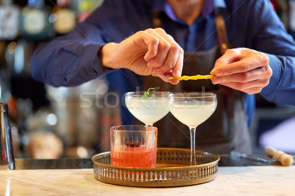 bartender with glass of cocktail and lemon at bar Stock photo © dolgachov