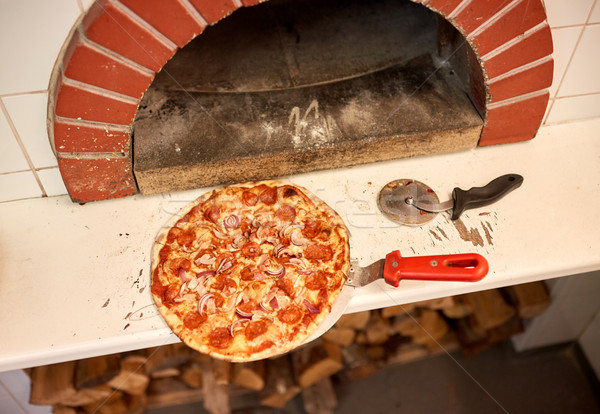 baked pizza on peel and cutter at pizzeria oven  Stock photo © dolgachov