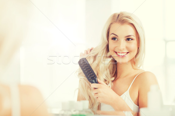 happy woman brushing hair with comb at bathroom Stock photo © dolgachov